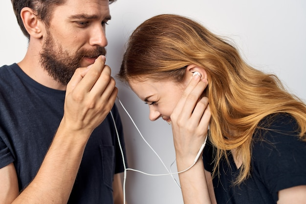 Jovem casal alegre com um telefone na mão e emoções no estilo de vida de estúdio de fones de ouvido