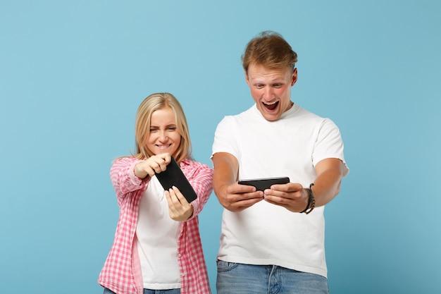 Jovem casal alegre dois amigos, homem e mulher, em camisetas brancas rosa em branco posando