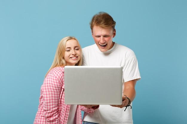 Jovem casal alegre dois amigos, homem e mulher em camisetas brancas rosa vazias em branco, posando