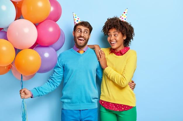 Jovem casal alegre e positivo em uma festa posando com balões