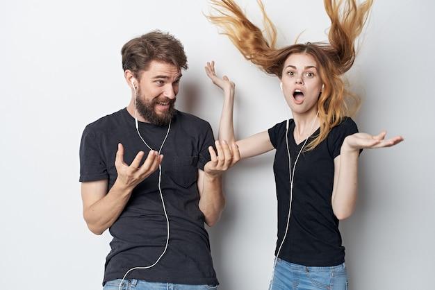 Jovem casal alegre em camiseta preta telefona diversão juntos amizade fundo isolado