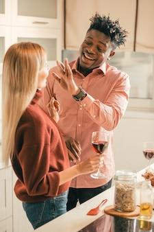 Jovem casal alegre em pé na cozinha bebendo vinho tinto enquanto o jovem tenta tocar o nariz da namorada
