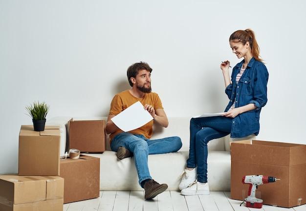 Jovem casal alegre em um apartamento com coisas em movimento