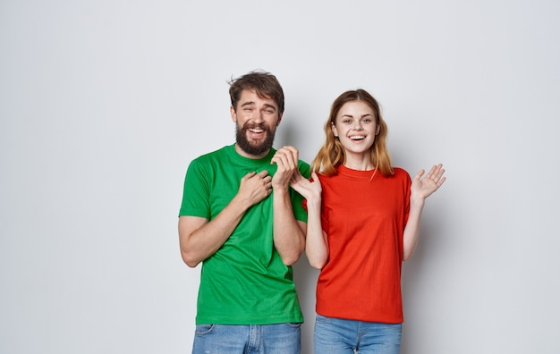 Jovem casal alegre no estúdio de amizade de emoções de comunicação de camisetas multicoloridas.