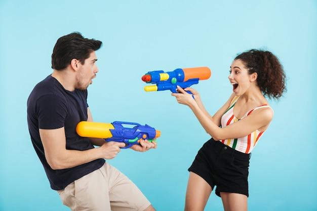 Jovem casal alegre parado isolado, se divertindo com armas de água