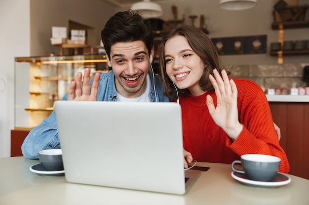 Jovem casal alegre sentado à mesa de um café