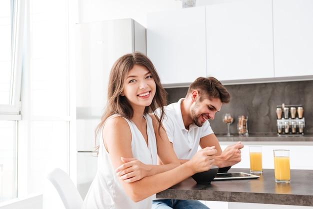 Jovem casal alegre sentado e tomando café da manhã na cozinha juntos