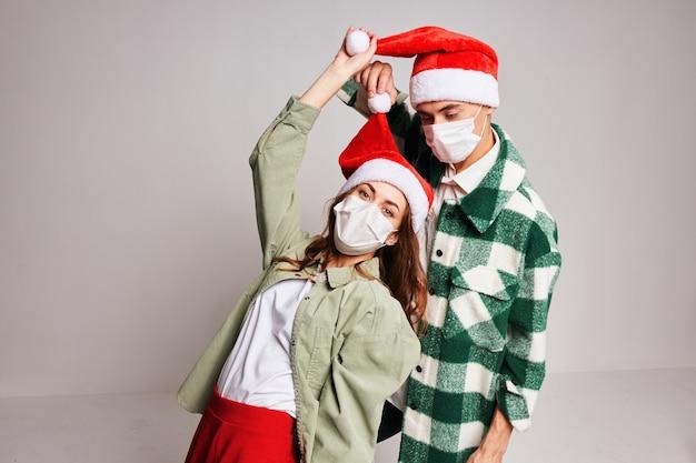 Jovem casal alegre vestindo roupas de ano novo, máscara médica, quarentena