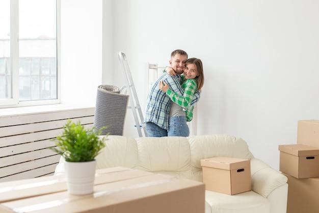 Jovem casal amoroso abraçando, regozijando-se em se mudar para sua nova casa. o conceito de movimento e