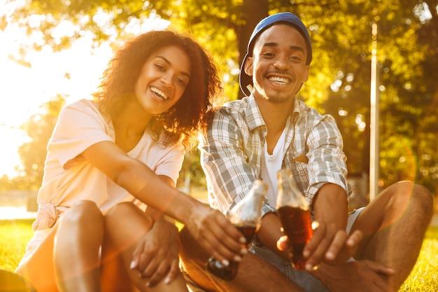 Jovem casal amoroso africano sentado ao ar livre no parque, bebendo refrigerante.