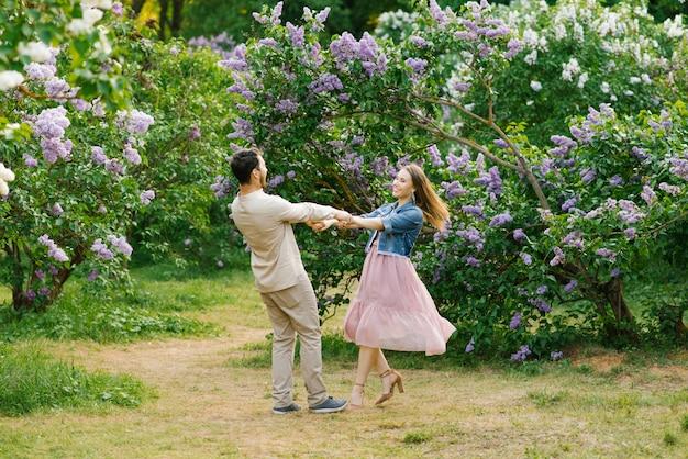 Jovem casal amoroso de mãos dadas e girando no jardim lilás na primavera