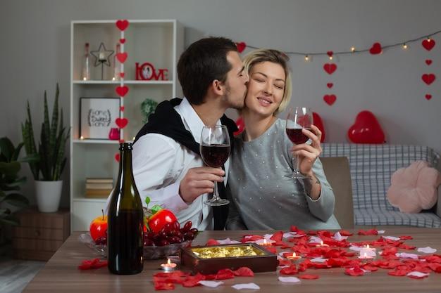 Jovem casal amoroso e feliz sentado à mesa comemorando o dia dos namorados em casa