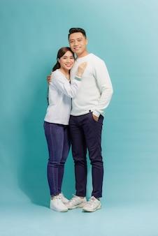 Jovem casal amoroso feliz abraçando isolado sobre o azul.