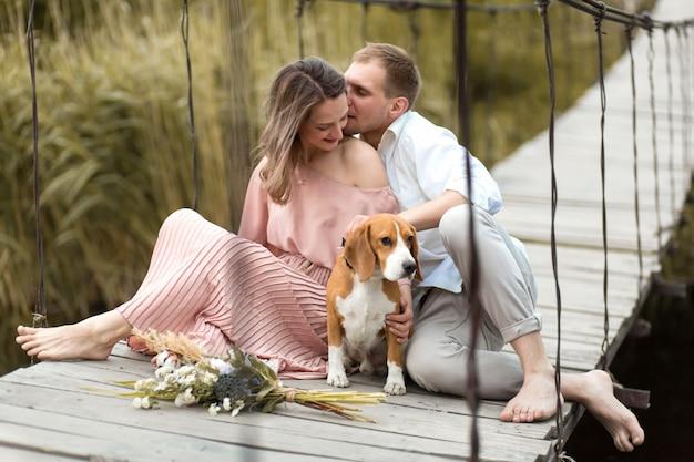 Jovem casal amoroso feliz abraçando na ponte sobre o rio com cachorro