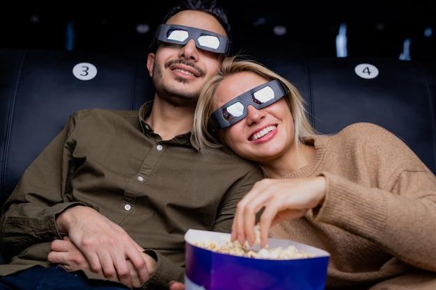 Jovem casal amoroso feliz em óculos 3d assistindo filme de ação interessante na tela grande enquanto relaxa no cinema
