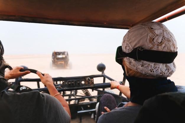 Jovem casal andando de carro de buggy no deserto