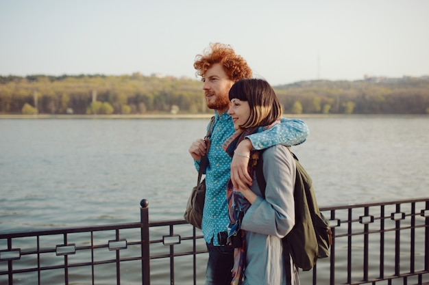 Jovem casal andando despreocupado no parque perto do lago