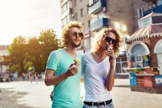 Jovem casal andando e lambendo sorvete