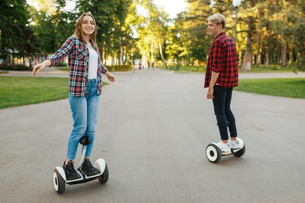 Jovem casal andando na mini placa giroscópica no parque de verão.