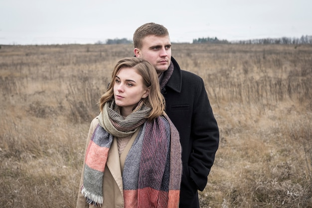 Jovem casal andando na zona rural de inverno em um dia frio e sombrio