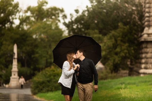 Jovem casal andando no parque em um dia chuvoso. história de amor em budapeste