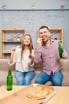 Jovem casal animado assistindo filme com cerveja e pizza