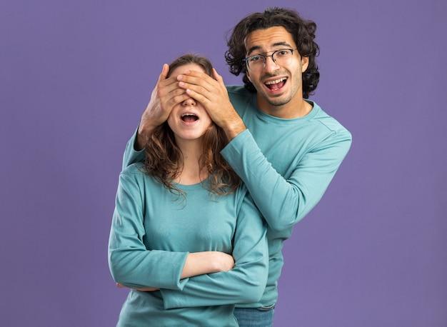 Jovem casal animado de pijama homem de óculos em pé atrás de uma mulher cobrindo os olhos com as mãos, olhando para a frente, mulher em pé com postura fechada isolada na parede roxa