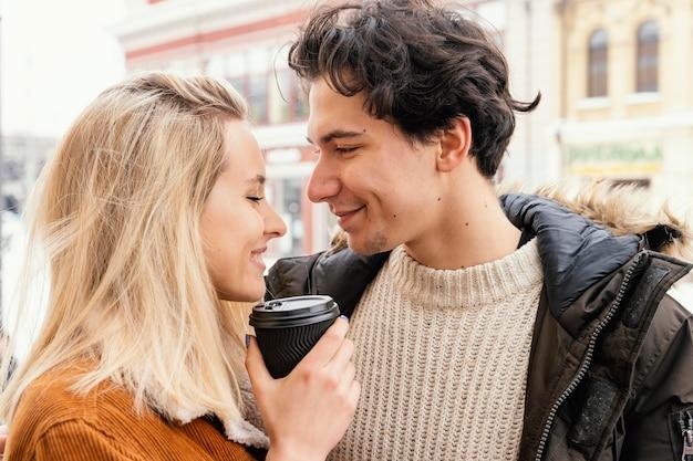 Jovem casal ao ar livre desfrutando de uma xícara de café
