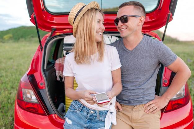 Jovem casal ao ar livre, explorar o mapa no telefone navigator sentado no porta-malas do carro com coisas para viajar