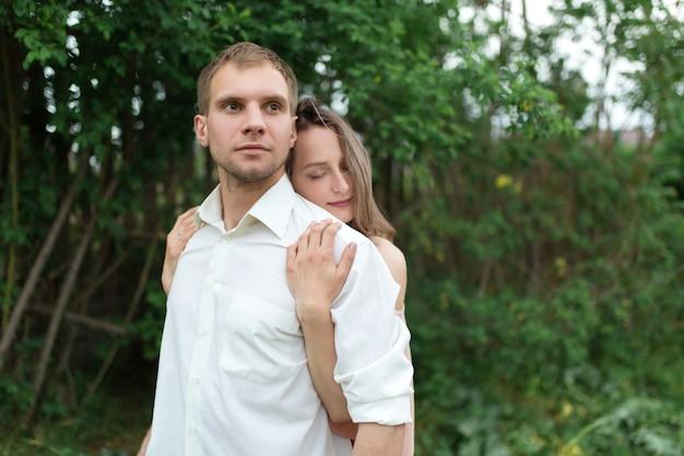 Jovem casal apaixonado, abraçando e dançando na grama verde no gramado