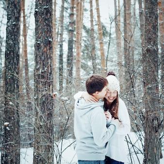 Jovem casal apaixonado, abraçando e se divertindo no inverno