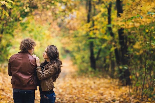 Jovem casal apaixonado, abraçando-se no parque outono.