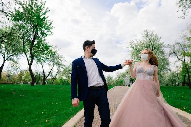 Jovem casal apaixonado andando com máscaras médicas durante a quarentena no dia do casamento
