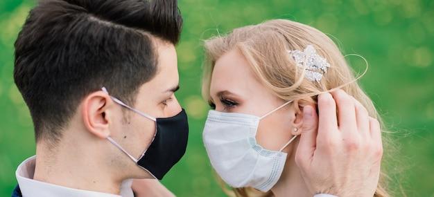 Jovem casal apaixonado andando com máscaras médicas no parque durante a quarentena no dia do casamento. coronavírus, doença, proteção, doente, doença, celebração da gripe na europa cancelada.