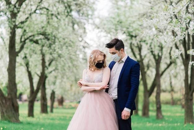 Jovem casal apaixonado andando com máscaras médicas no parque durante a quarentena no dia do casamento. coronavírus, doença, proteção, doente, doença, comemoração da gripe na europa cancelada.
