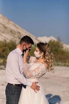 Jovem casal apaixonado andando com máscaras médicas no parque durante a quarentena no dia do casamento.