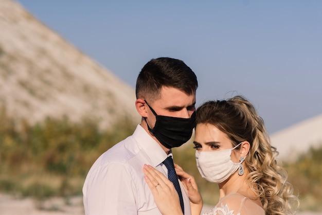 Jovem casal apaixonado andando com máscaras médicas no parque durante a quarentena no dia do casamento. Foto Premium