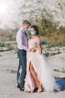 Jovem casal apaixonado andando com máscaras médicas no parque durante a quarentena