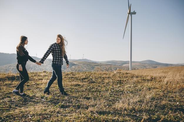 Jovem casal apaixonado andando no parque outono segurando as mãos olhando o pôr do sol.