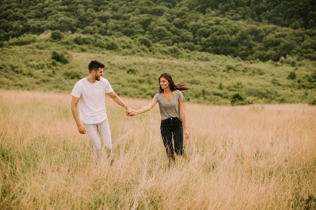 Jovem casal apaixonado andando pelo campo de grama