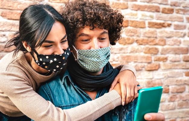 Jovem casal apaixonado assistindo celular inteligente usando máscara facial