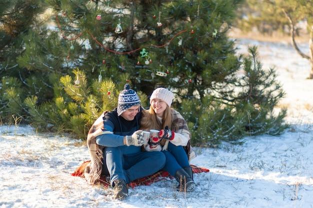Jovem casal apaixonado bebe uma bebida quente com marshmallows, sentado no inverno na floresta, aconchegando tapetes quentes e confortáveis e aprecia a natureza