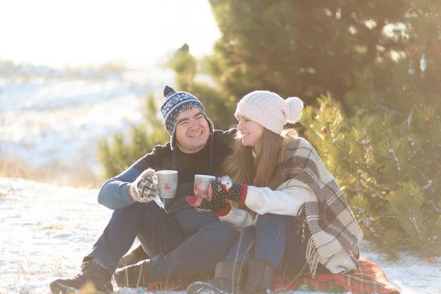 Jovem casal apaixonado bebe uma bebida quente com marshmallows, sentado no inverno na floresta