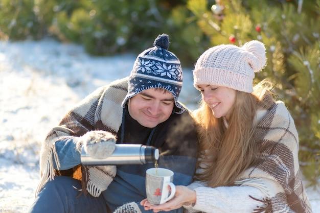 Jovem casal apaixonado bebe uma bebida quente de uma garrafa térmica, sentado no inverno na floresta, aconchegante