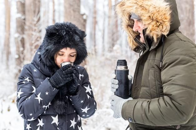 Jovem casal apaixonado bebe uma bebida quente em uma garrafa térmica e aproveita a natureza no inverno.
