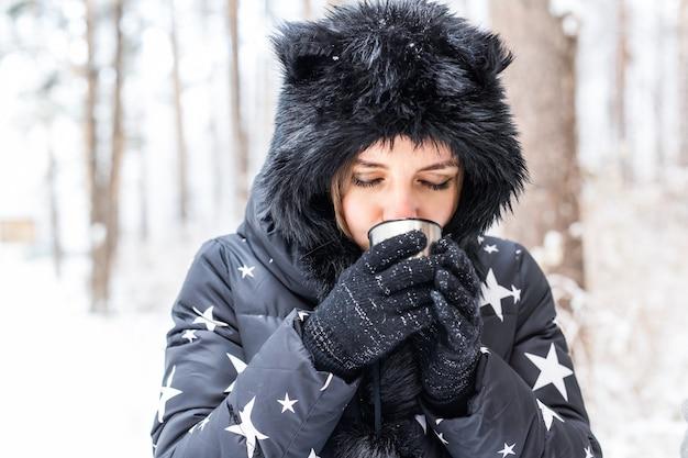 Jovem casal apaixonado bebe uma bebida quente em uma garrafa térmica e aproveita a natureza no inverno