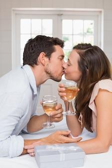 Jovem casal apaixonado beijando com taças de vinho