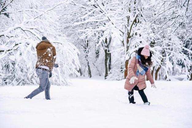 Jovem casal apaixonado brincando com bolas de neve em um parque de inverno