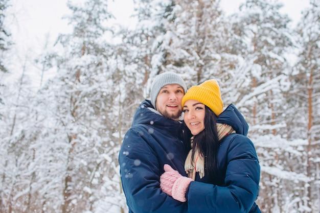 Jovem casal apaixonado caminha pela floresta de inverno, um casal se abraça e ri em um fundo de uma floresta de neve