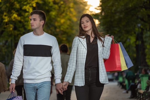 Jovem casal apaixonado, caminhando no parque, garota segurando sacolas de compras.